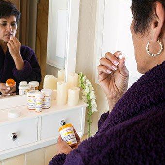 A womanin a bathroom taking pills.
