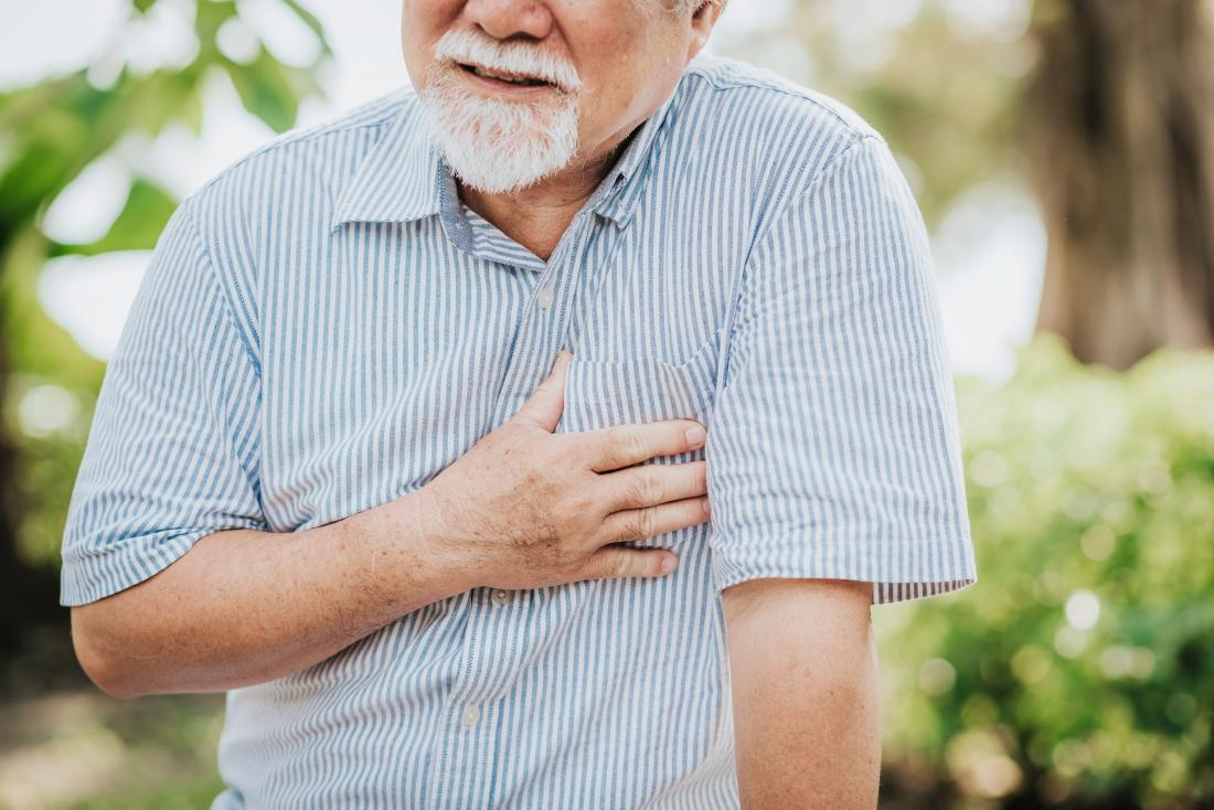 Senior man holding his chest because of heart pain