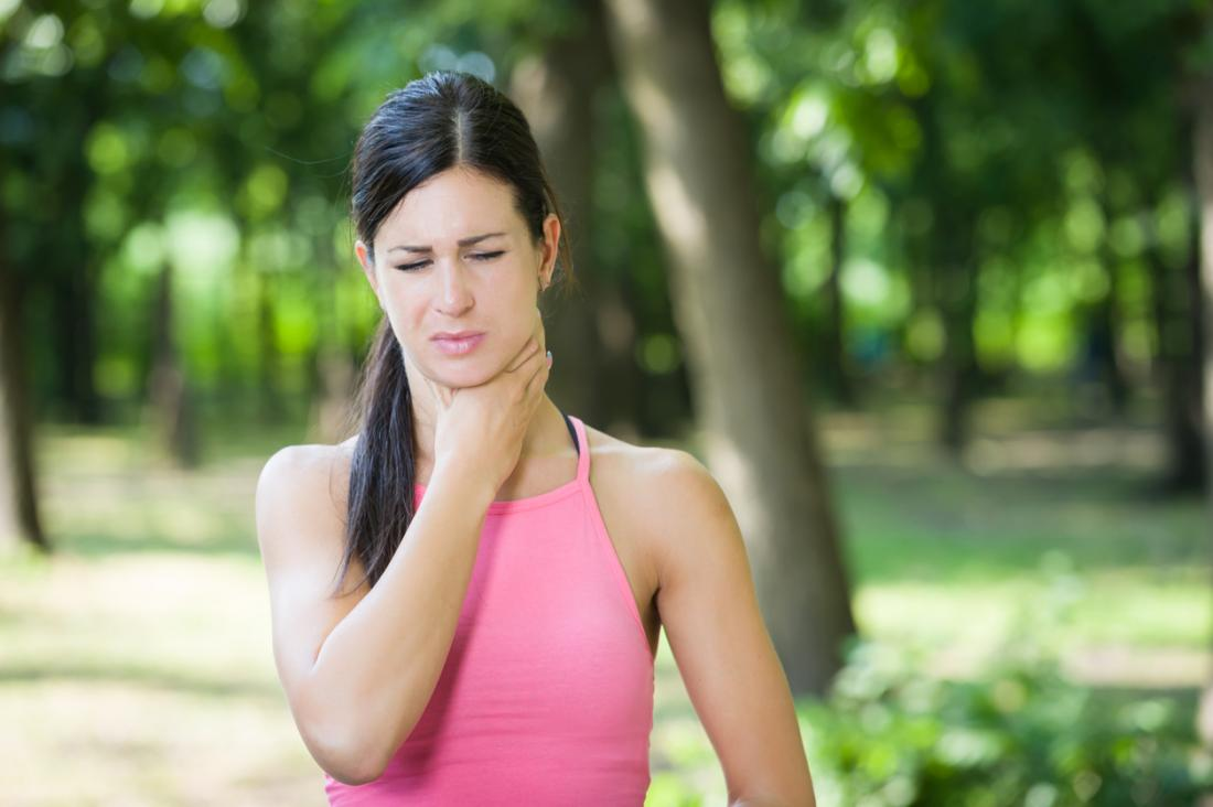 Woman having trouble breathing holding throat