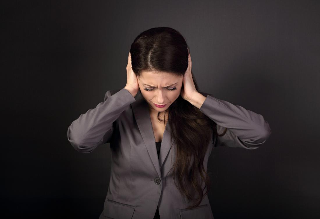 Woman holding head in pain due to double ear infection