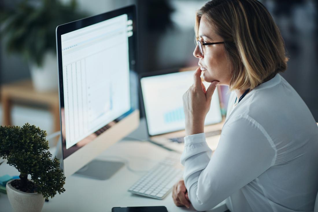 woman looking at computer monitor screens at work.