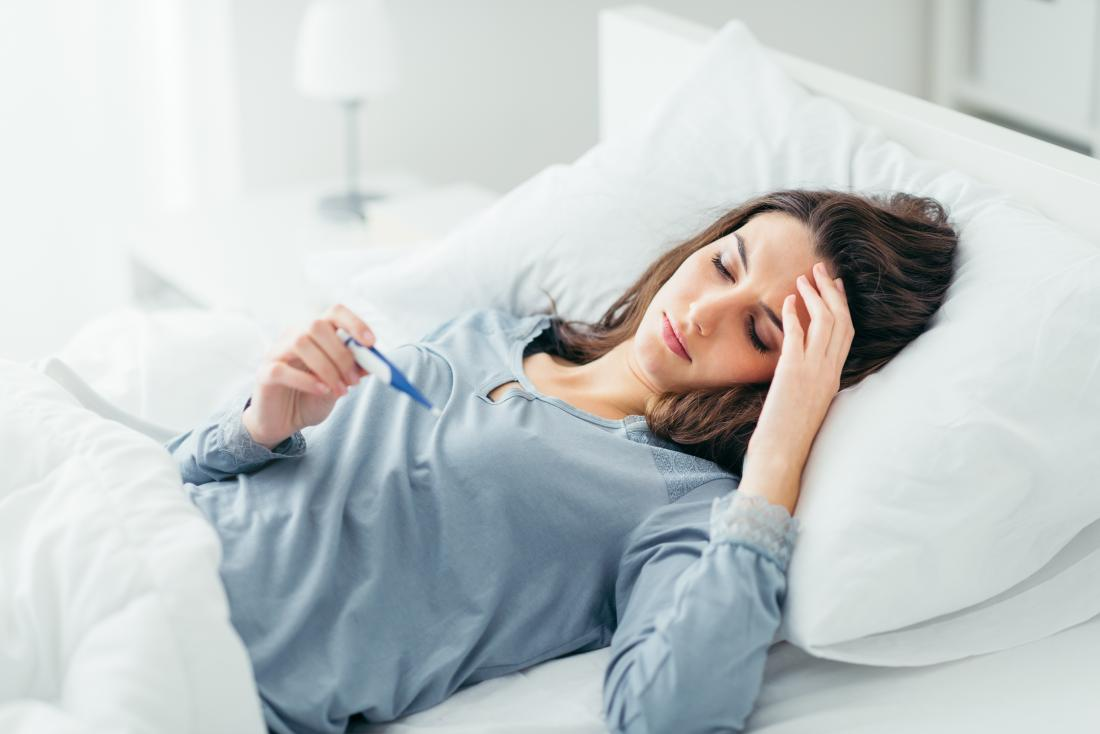 Woman in bed measuring temperature with fever.