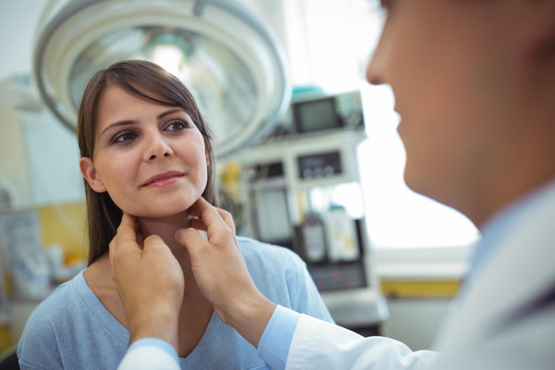 Doctor examining patients neck to diagnose multinodular goiter