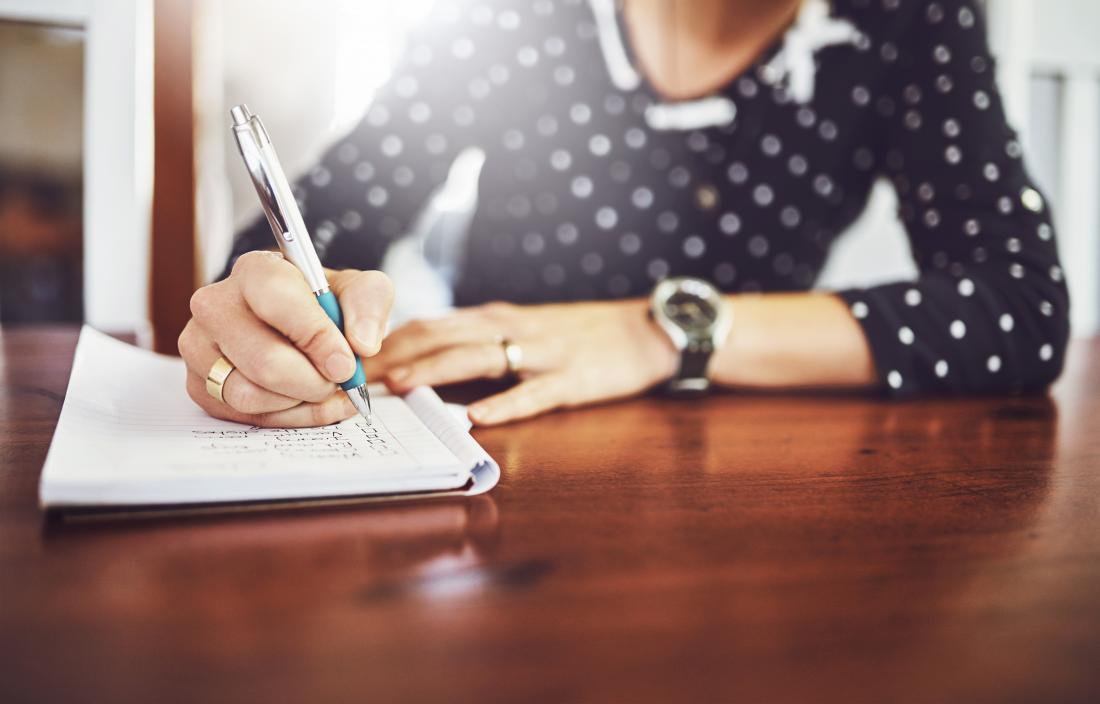 Person writing notes in notepad diary or journal book on table.