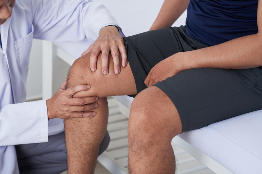 Doctor examining knee to diagnose tricompartmental osteoarthritis