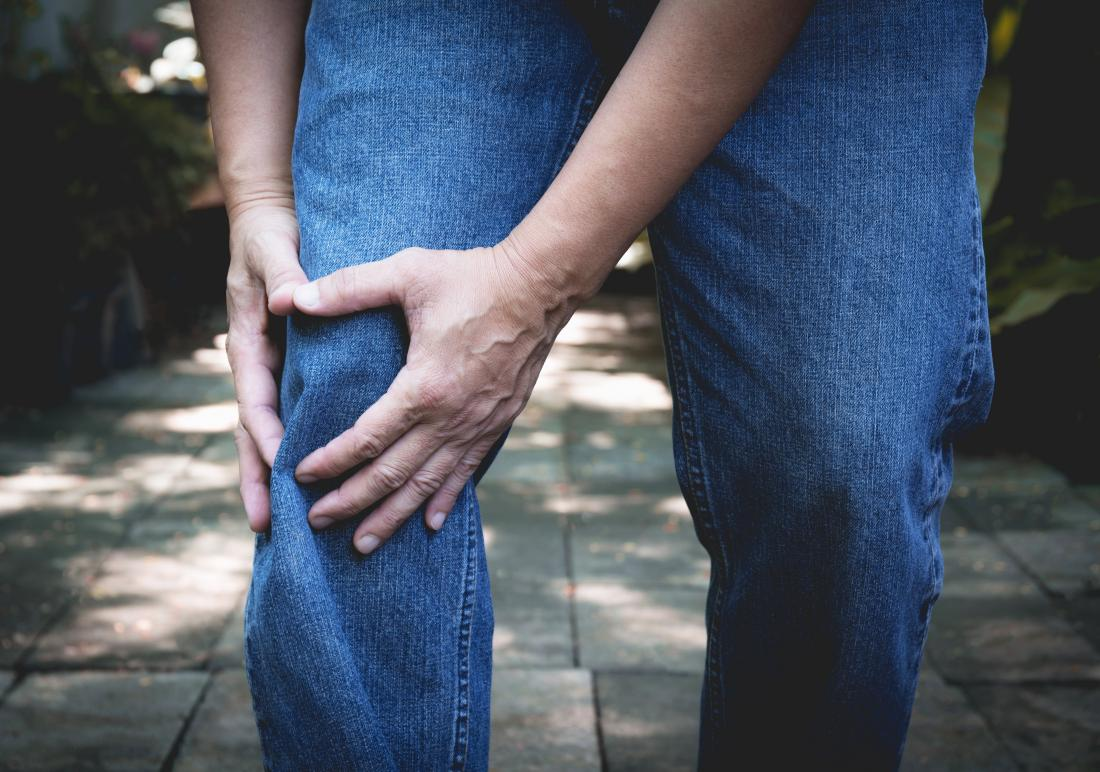 Man holding his knee due to tricompartmental osteoarthritis