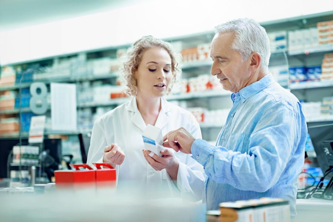 Man discussing prescription medication with pharmacist.