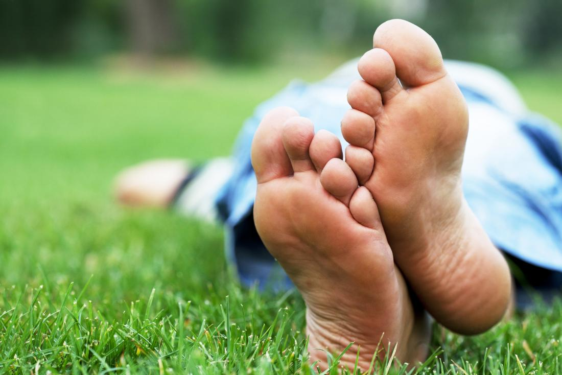 Bare feet of person lying on grass.