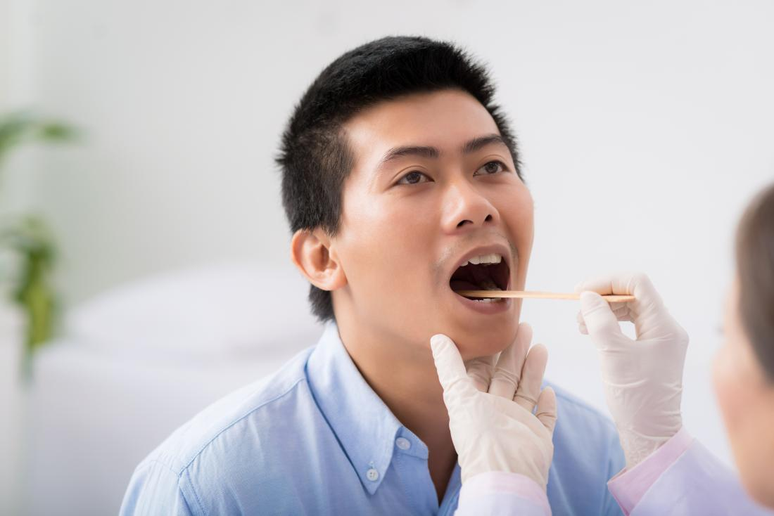 Man having bleeding tongue and throat inspected by doctor using tongue depressor.