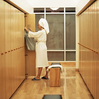 A woman changes in a locker room after a shower.
