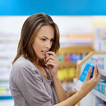 A woman shops for over-the-counter (OTC) vaginal yeast infection medication at a pharmacy.