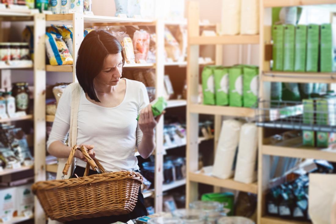 woman shopping for food reading ingredients label.