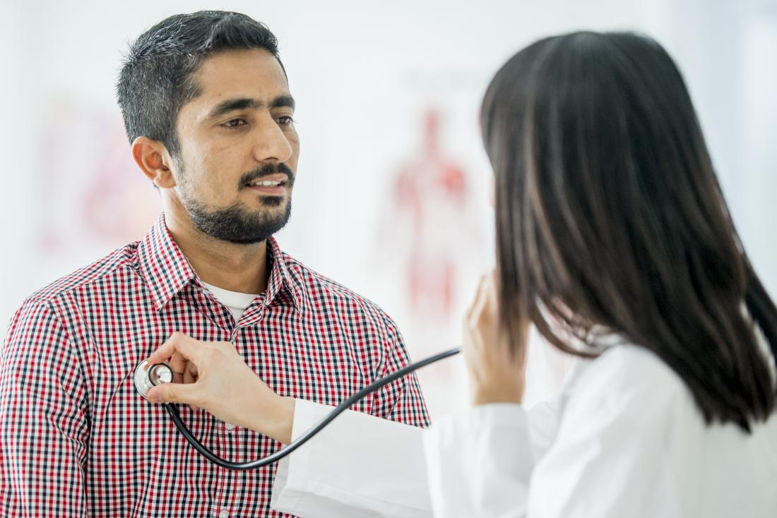 Doctor using stethoscope listening to patients breathing.