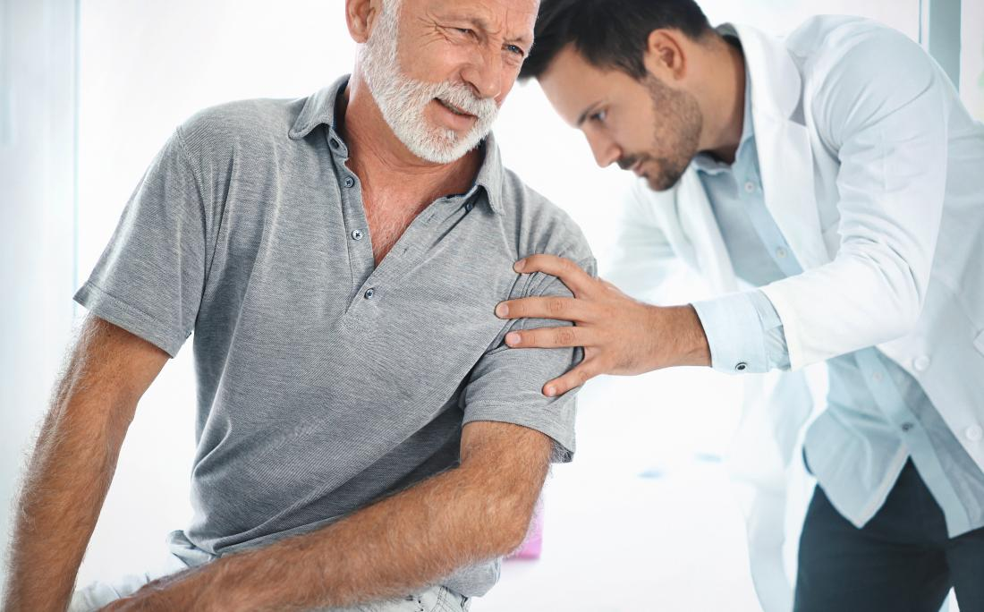 Doctor performing physical examination of older mans back