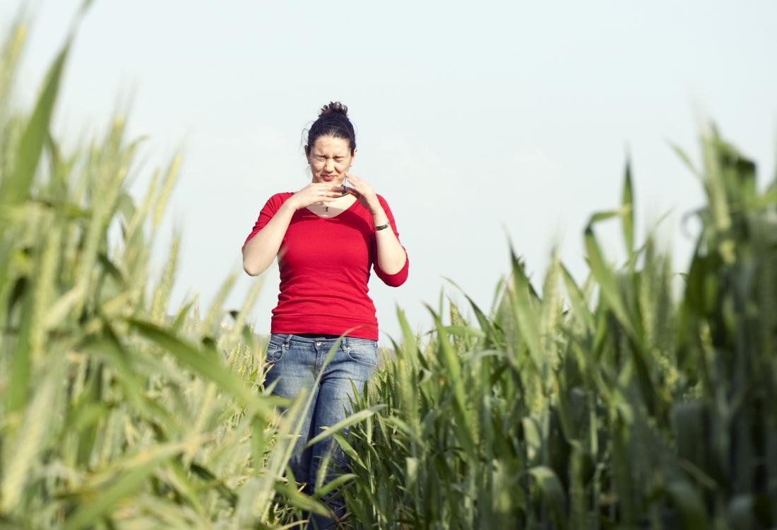 young woman with allergy walking through field