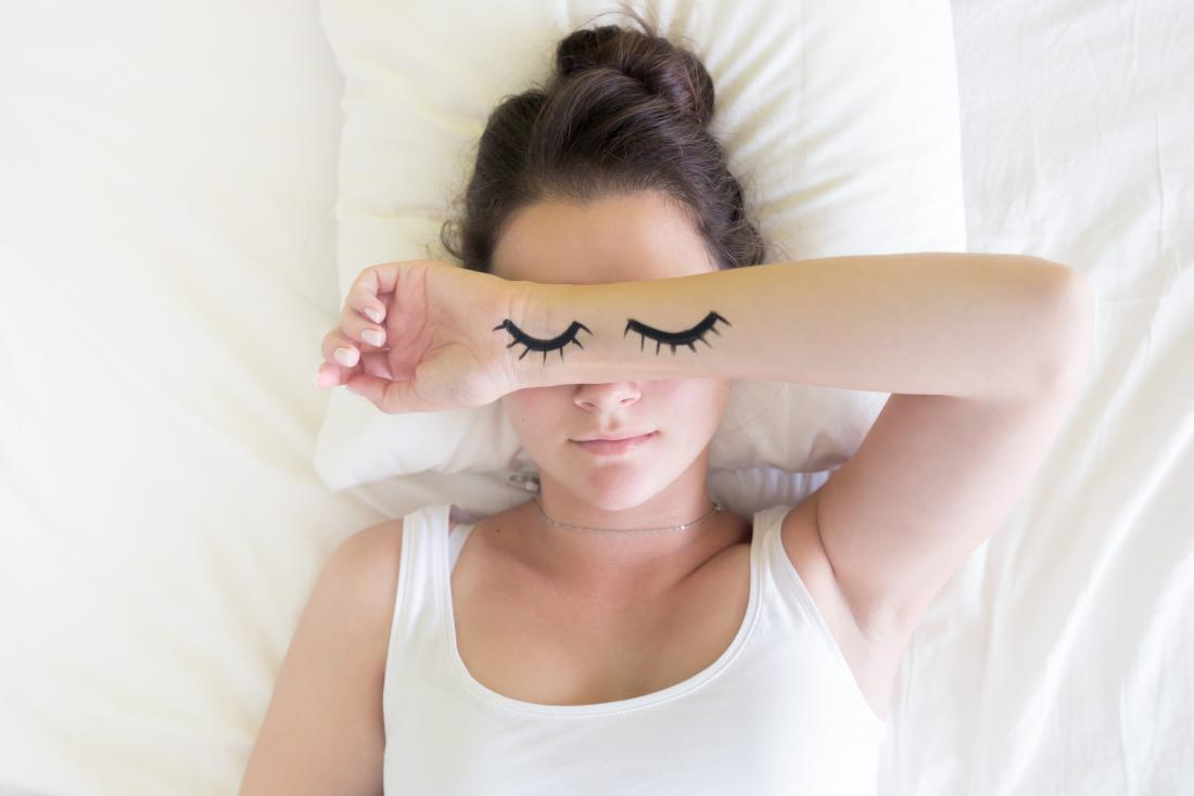 young person sleeping with eyelids drawn on her arms