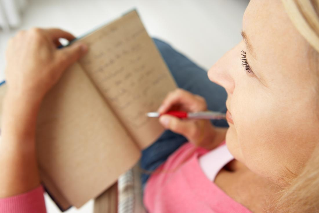 Lady writing notes because of memory loss due to early onset alzheimer's