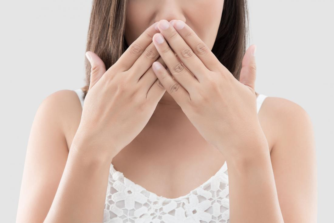 Woman covering her mouth and wondering why breath smells like urine