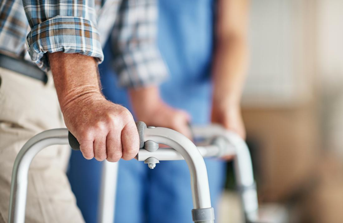 Man walking with zimmer frame walker with nurse helping.