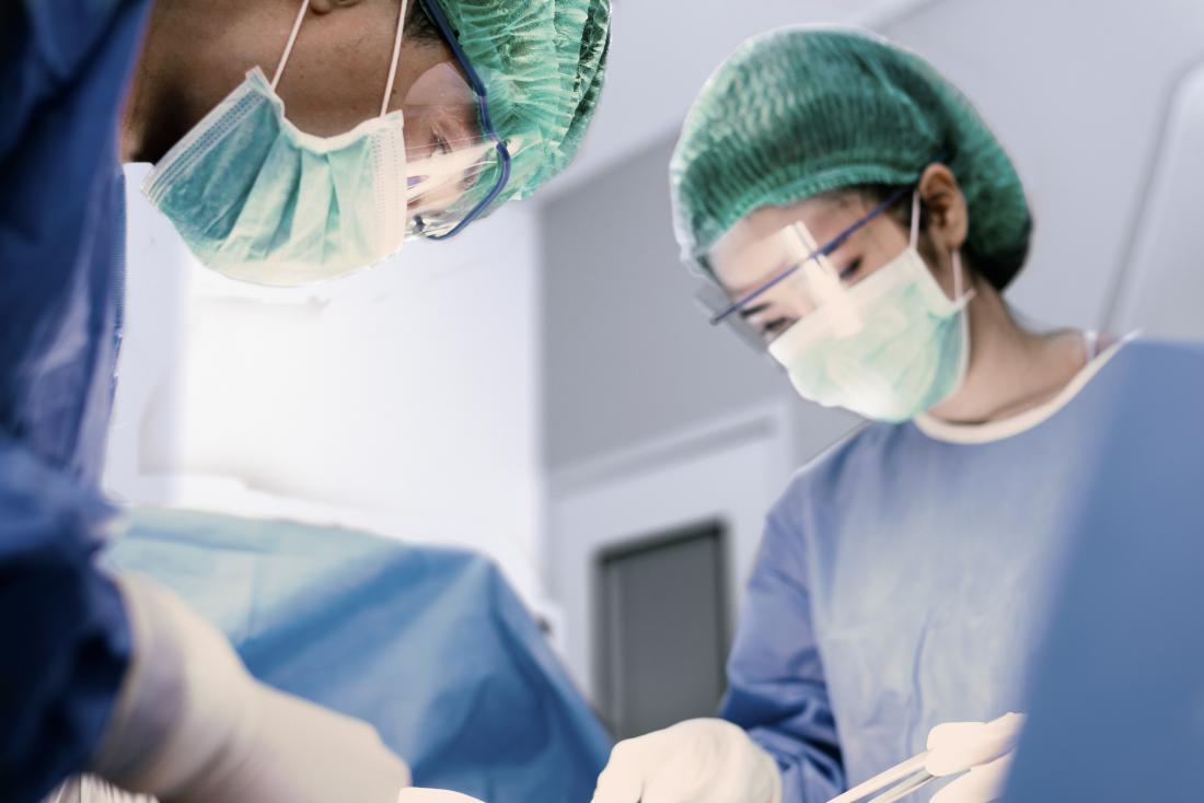 Surgery taking place in operating room with two surgeons.