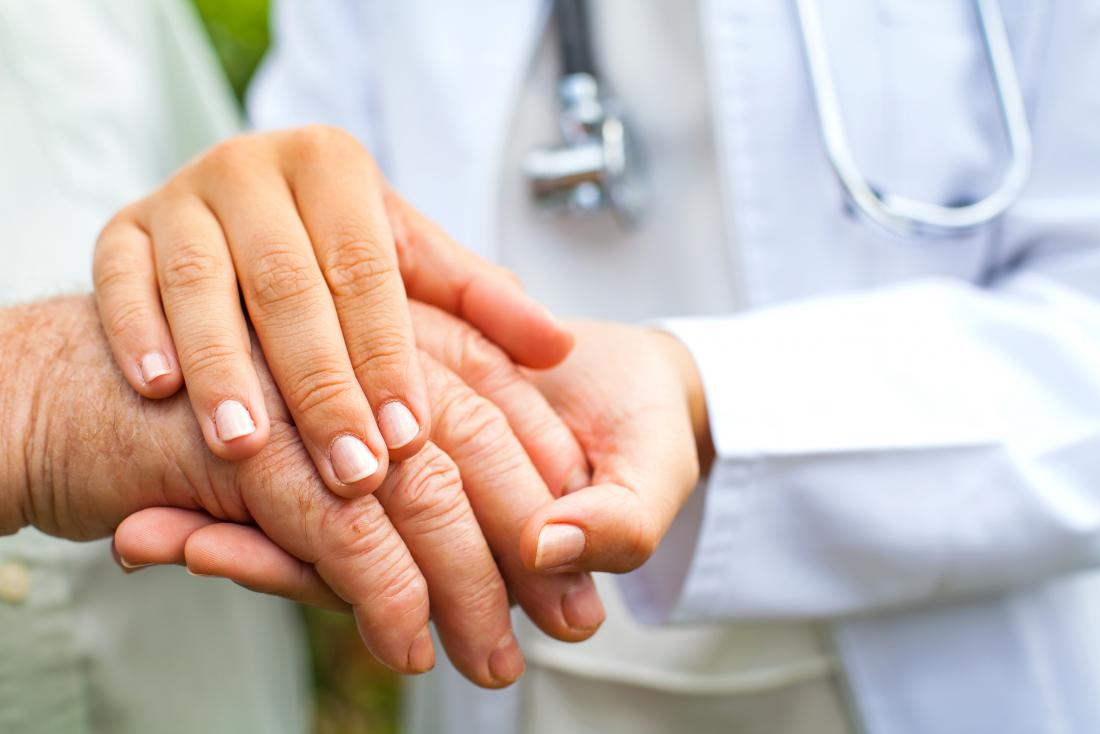 Doctor holding older person's hands because of tremors and shakiness