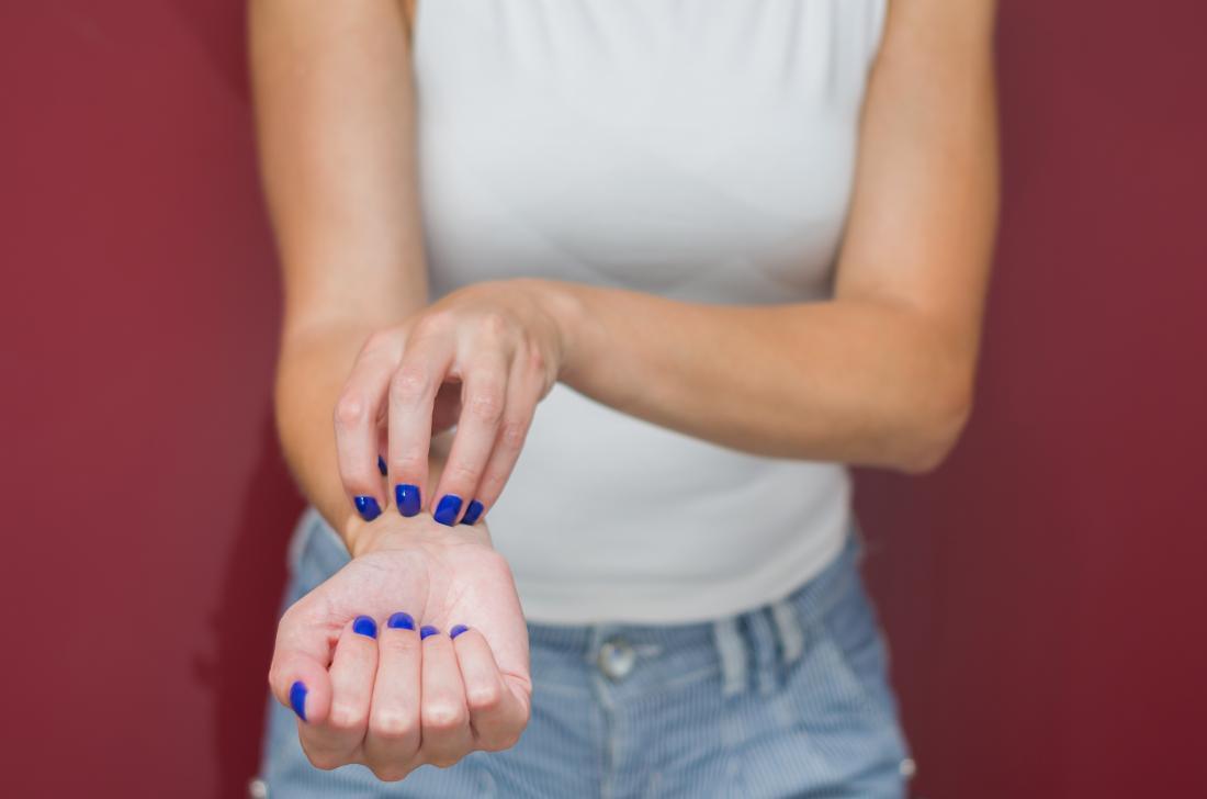 Woman itching wrist because of rash.
