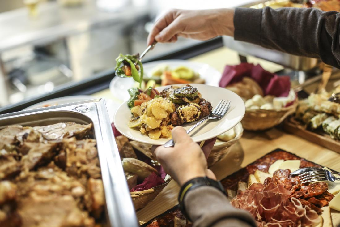 Person helping themselves to various foods from a buffet.