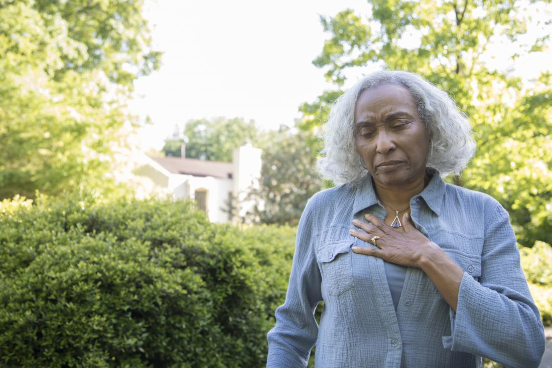 Mature post-menopausal woman with chest pain and outdoors hand on breast.