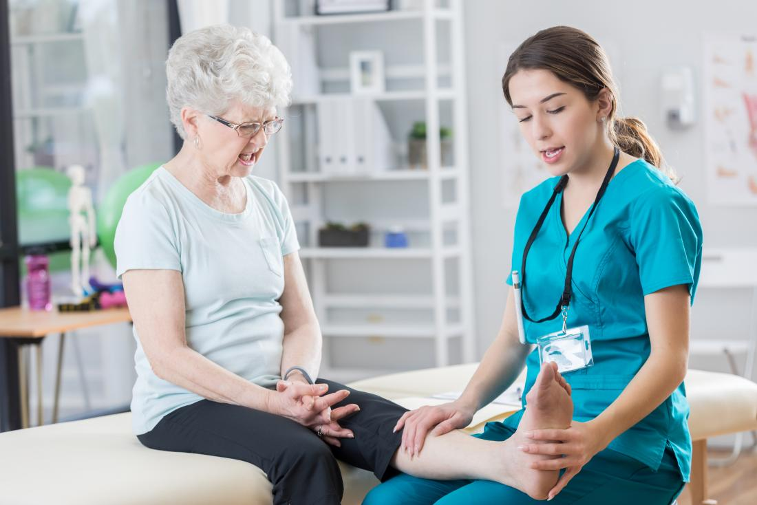 Senior woman having leg looked at by physiotherapist.