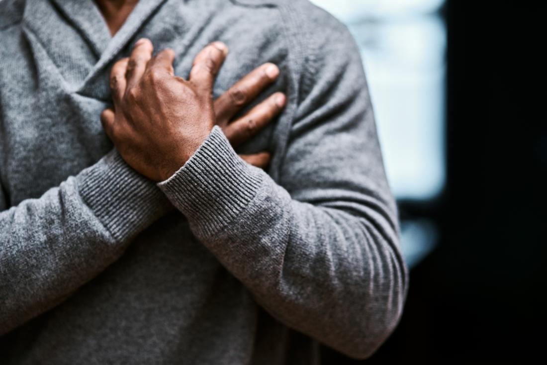 person holding both hands over heart because of chest pains