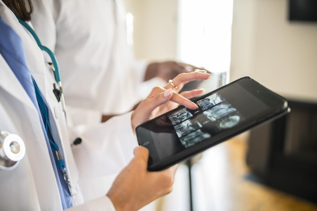 Doctor looking at CT scans on tablet.