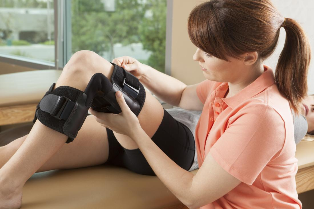 person receiving knee and leg brace form physical therapist