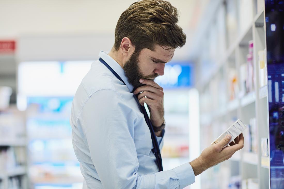 Pharmacist looking at pack of medicine