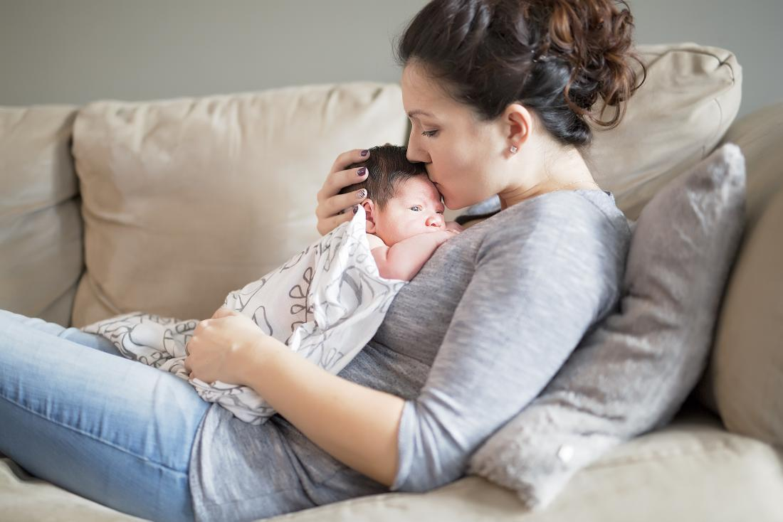Woman lying on sofa holding baby on chest