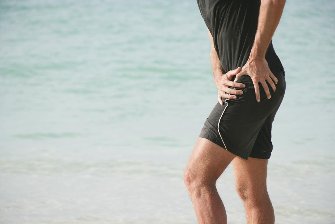 Runner clutching his hip in pain.