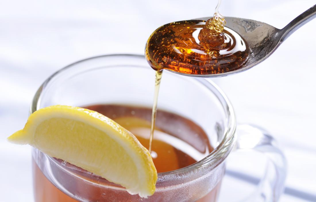 Honey being drizzled onto spoon and into mug of tea with lemon slice.