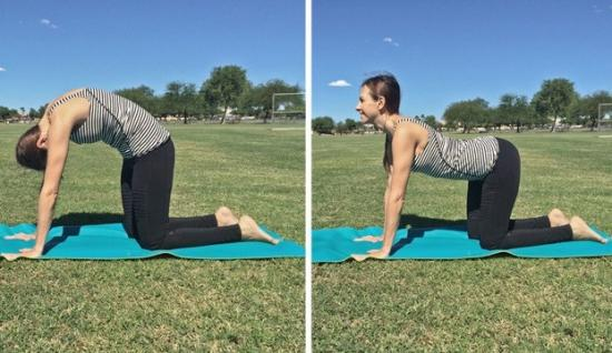 Woman performing cat cow yoga pose outdoors