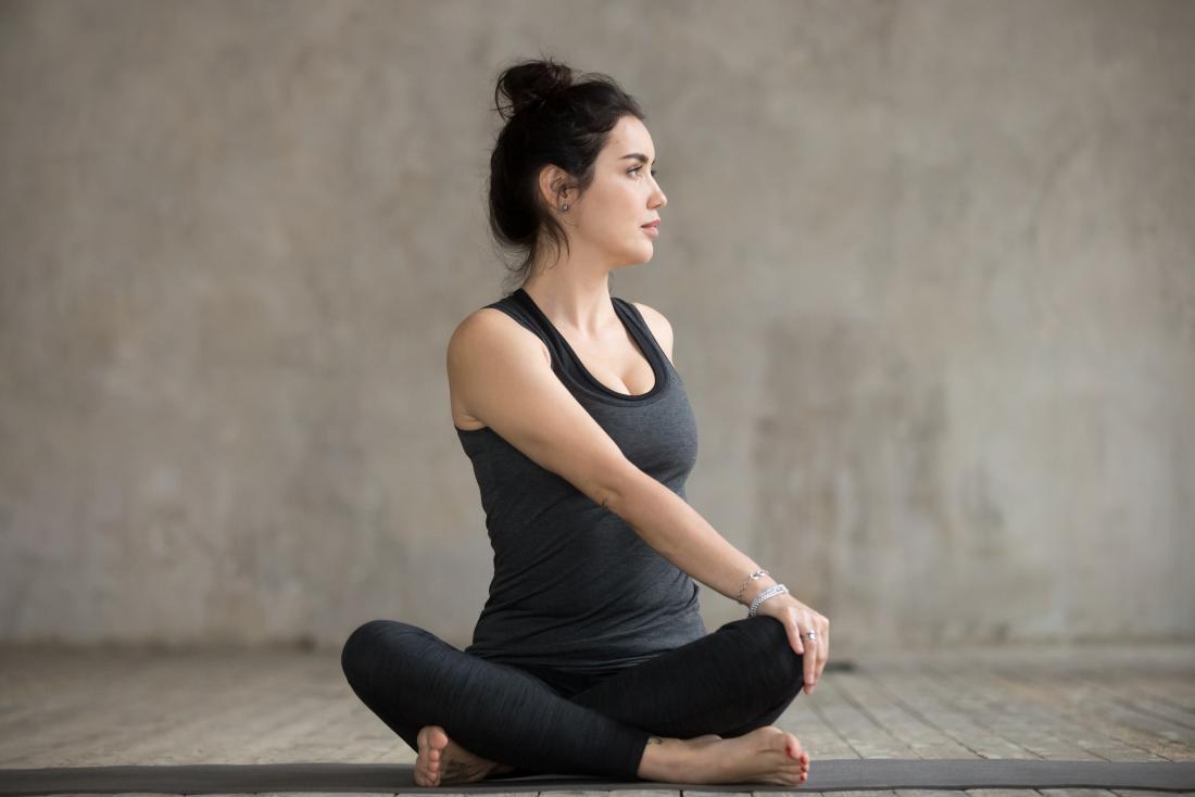 Parivrtta Sukhasana yoga pose also known as sitting back stretch, twist, or turn