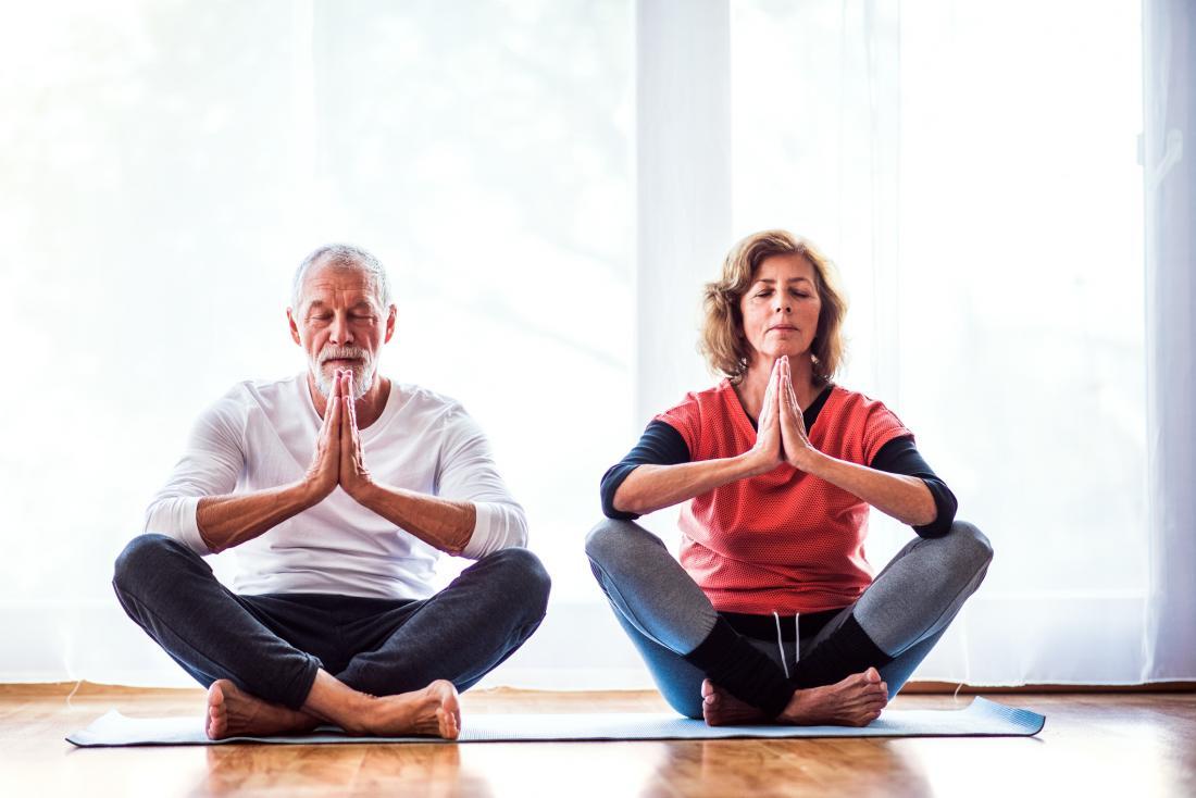 senior man and woman meditating