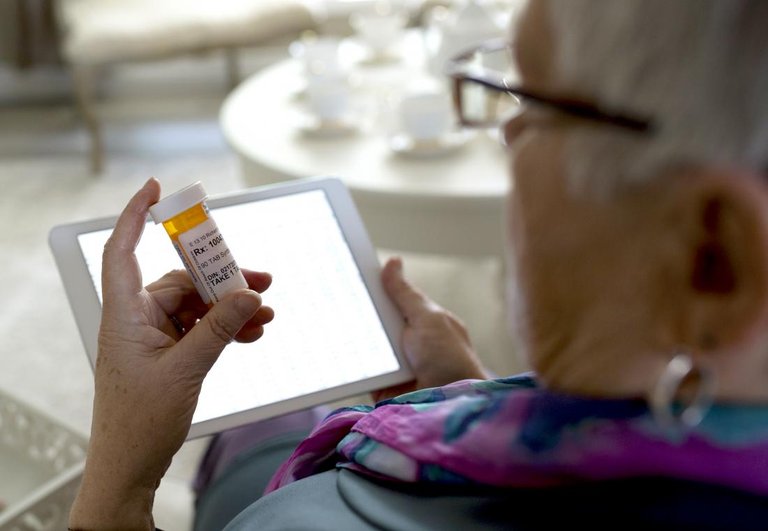 Senior woman holding bottle of pills in front of tablet.