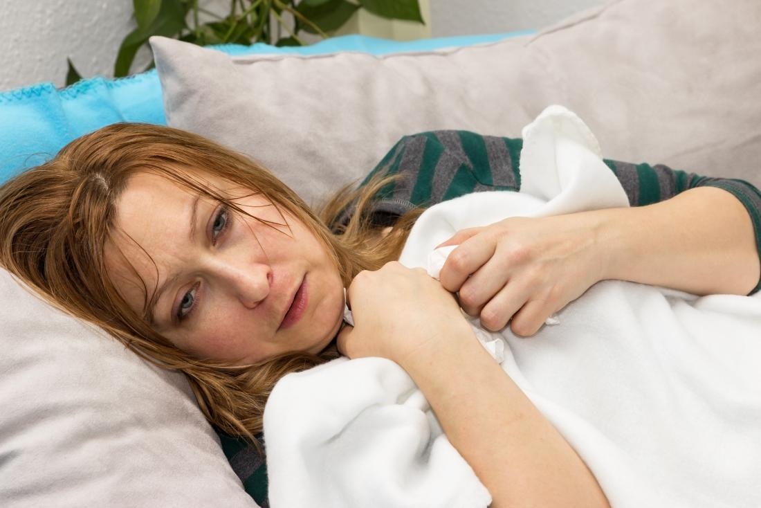woman on sofa with blanket suffering from fever sweating and chills