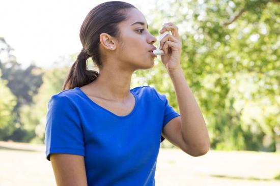 Woman with asthma using inhaler outside