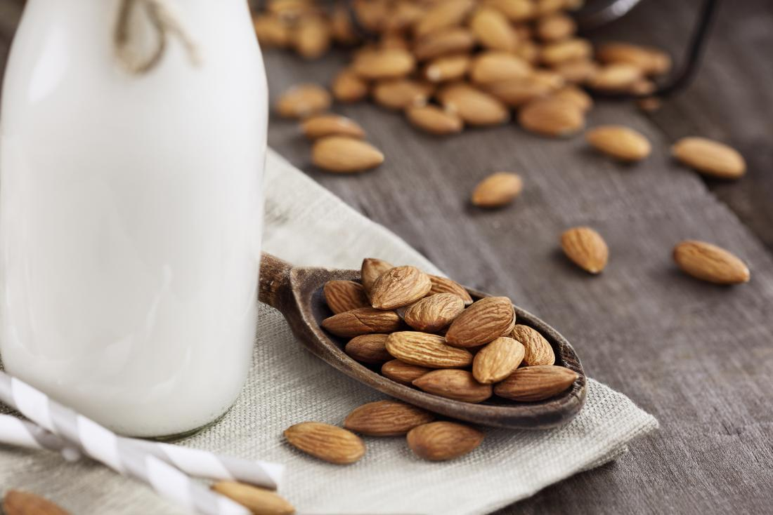 Almonds on a wooden spoon and almond milk
