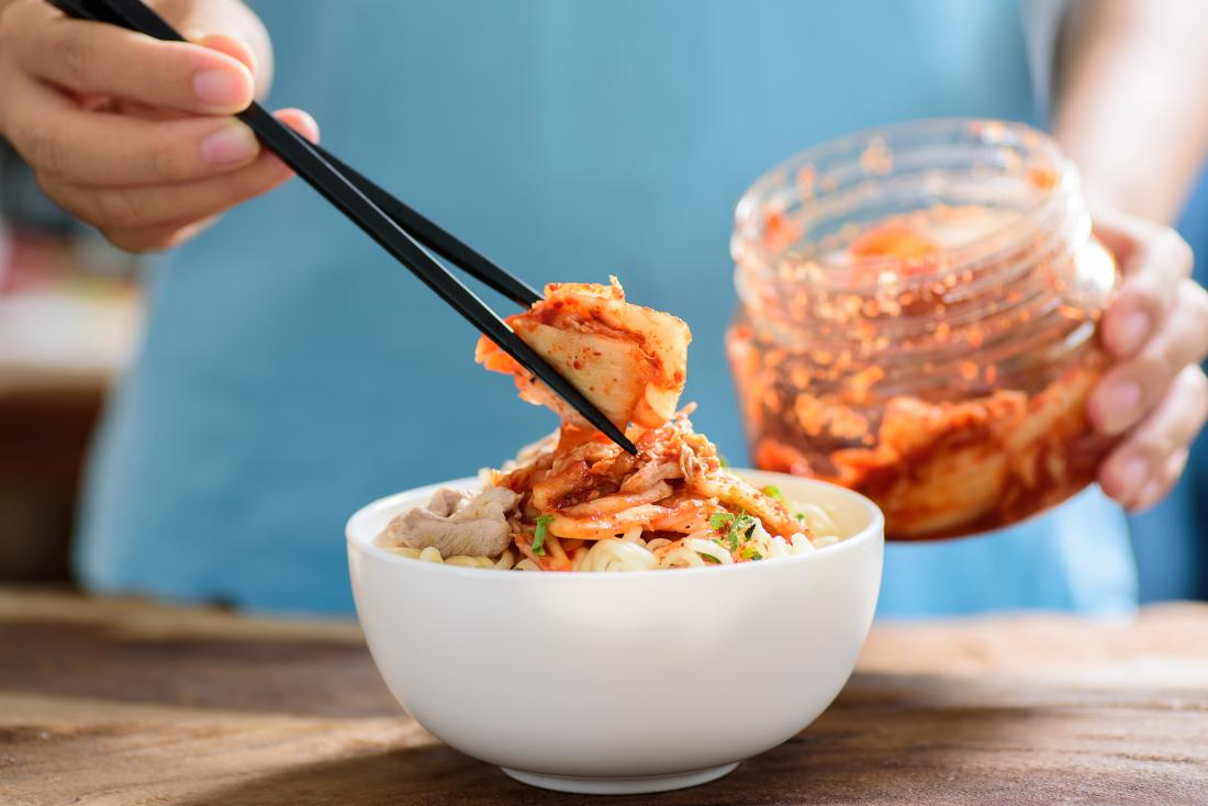 Probiotics for crohns shown by person putting kimchi in bowl