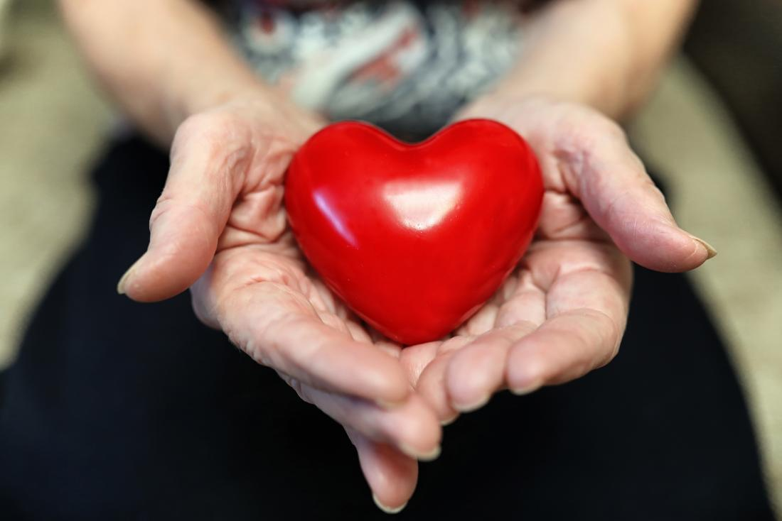 person holding heart figurine