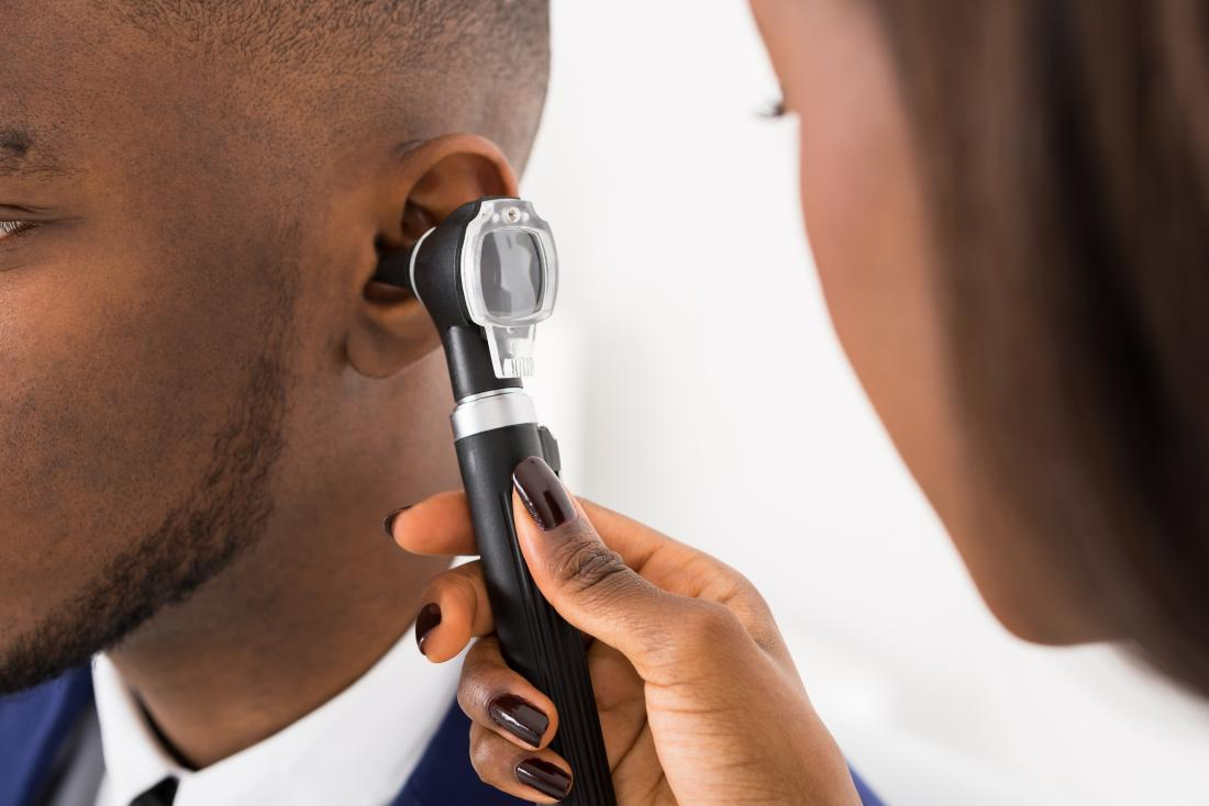 Doctor inspecting patient's ear.