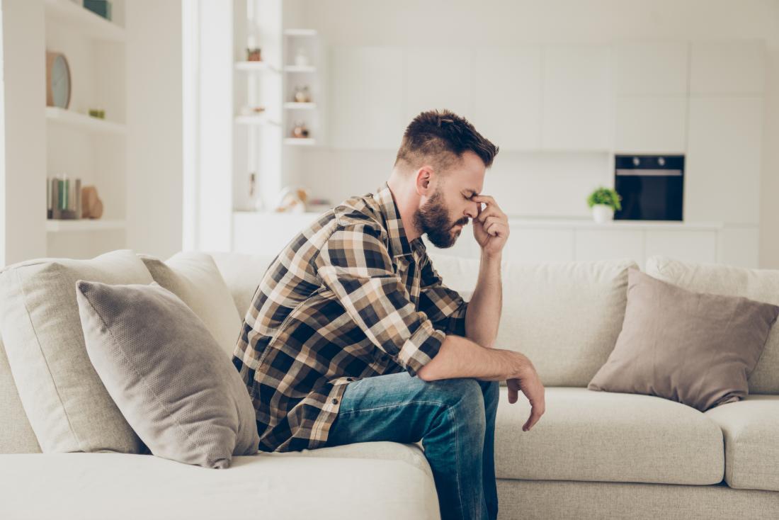 man with a headache sat on his sofa