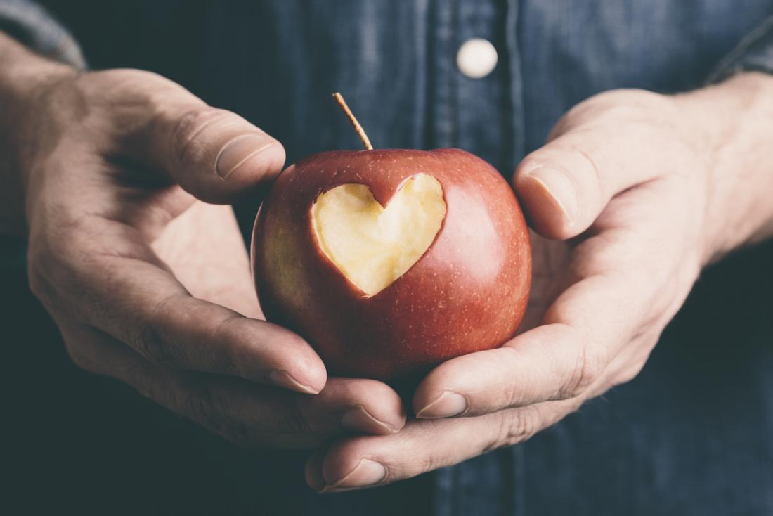 Apple being held in man's hands with heart shape cut out of it.