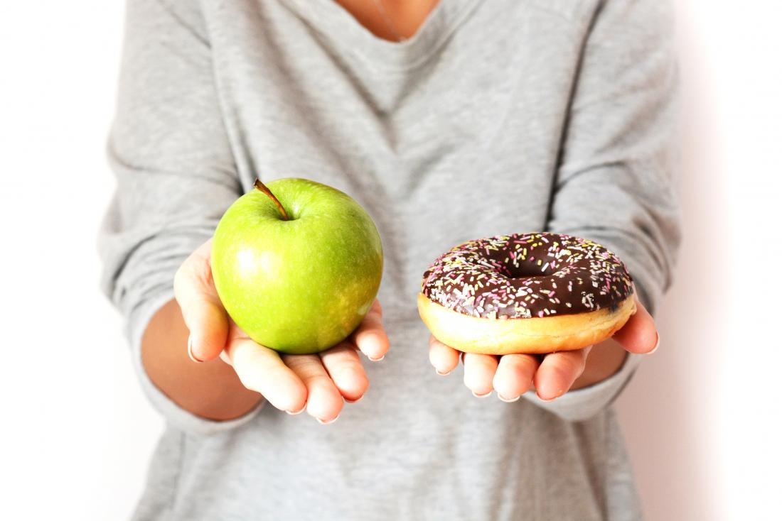 Person holding an apple and a donut