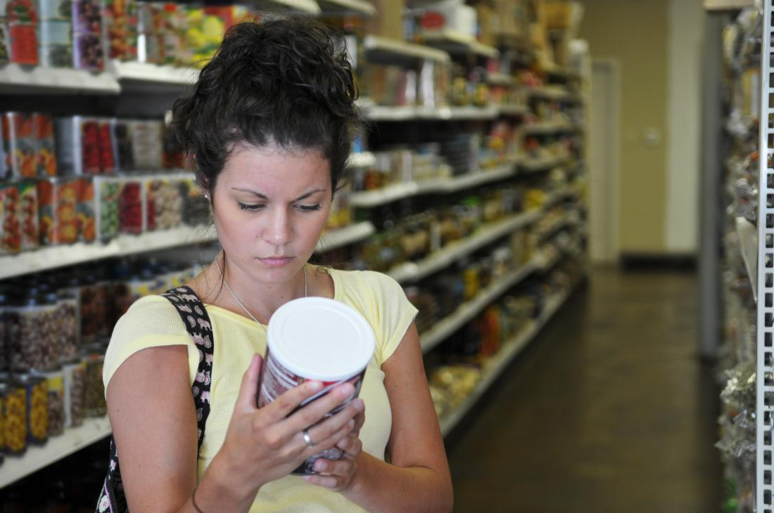 woman checking ingredients on food container